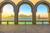 Modern skyscrapers of Doha West Bay skyline at sunset light through arches of museum located along Corniche in Qatari capital. Doha in Qatar. Middle East, Arabian Peninsula in Persian Gulf.