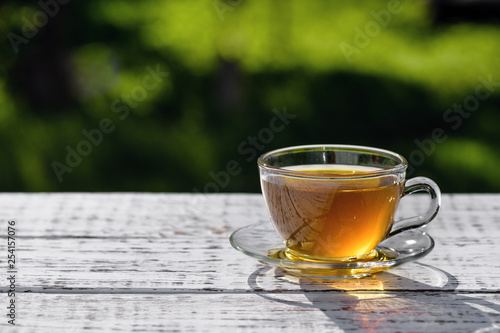 Foto auf AluDibond Tee Green tea. Cup of tea with a saucer, standing on a wooden, white table, outdoors, in the rays of sunlight.