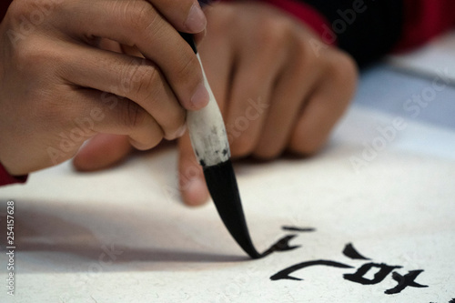 Fototapeta japanese woman writing ideograms with brush
