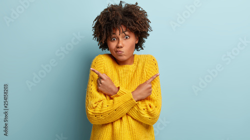 Fotomural  Puzzled confused woman has hesitant expression, curly hairstyle, crosses hands o