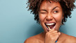 Leinwandbild Motiv Close up shot of happy joyful funny dark skinned young woman has Afro hair brushes teeth actively with toothbrush, opens mouth broadly, blinks eye, shows bare shoulders, cares of oral hygiene