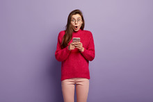 Half Length Shot Of Surprised Woman Holds Mobile Phone, Writes Notes In Gadget, Being Distracted By Bad News, Has Dark Long Hair, Dressed In Casual Outfit, Uses Wireless Internet. Modern Communication