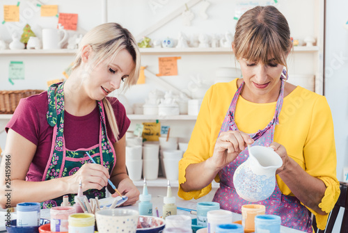 Photo Two women painting own ceramic tableware in DIY workshop