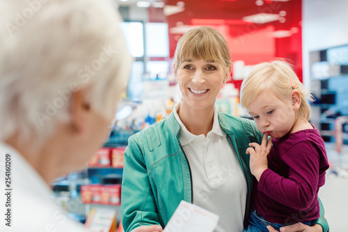 In de dag Apotheek Mother with daughter in pharmacy at the counter