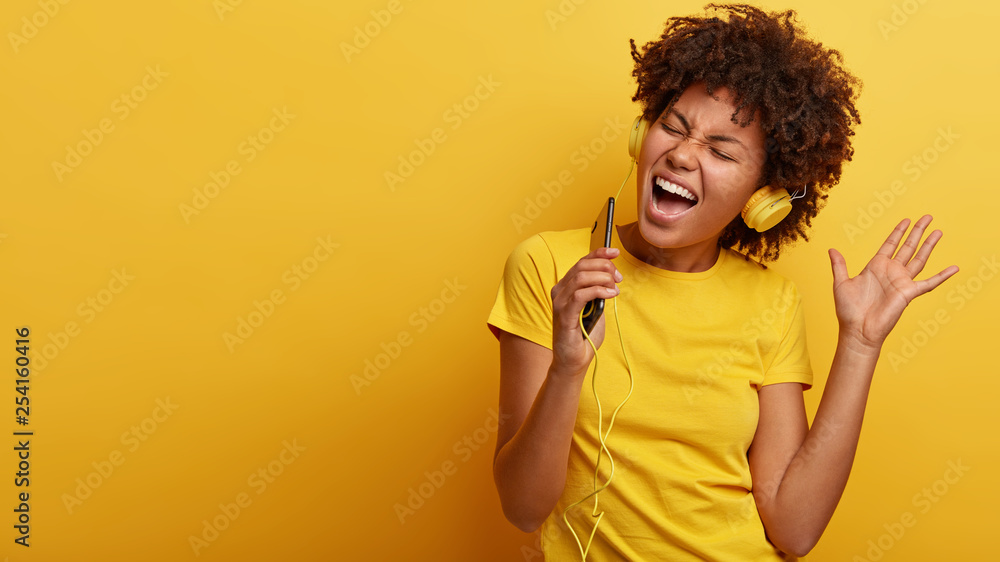 Fototapeta Yeah, I am pleased. Joyful lovely dark skinned woman raises hand in dance move, likes great sound in new headphones, sings loudly, carries cellular, smiles broadly, wears yellow casual clothes