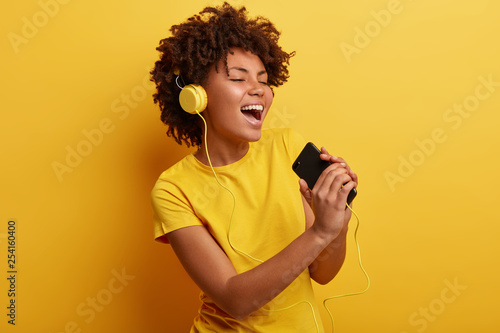 Joyful optimistic glad black woman glad to search favourite composition on web page, listens favourite cool song in headphones, sings from pleasure, has modern gadgets, wears yellow t shirt. - 254160400