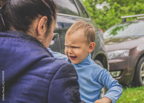 Vászonkép  Naughty child make faces in front of mom