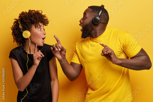 Happy dark skinned students look surprisingly at each other, listen music of same genre, sing favourite melody, listen new composition, filled with positive emotions, wears t shirt, isolated on yellow - 254160663