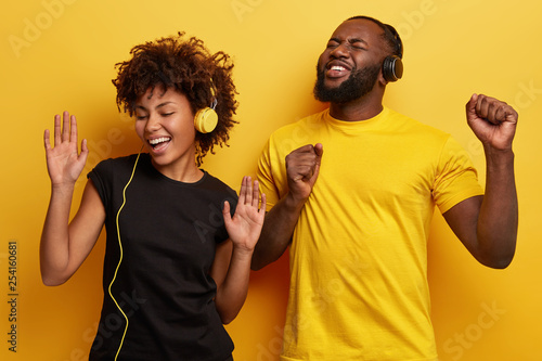 Photo of joyful positive ethnic female and male teenagers sing from pleasure, gesture actively, listen music from playlist, enjoy perfect sound, stand next to each other, isolated over yellow wall - 254160681