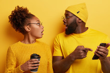 Shocked Black Woman And Man Impressed While Scroll Social Media Page. Emotioanl Lady With Crisp Hair Hears Shocking Newsfrom Friend Who Indicates At Cell Phone Screen, Holds Paper Cup Of Beverage
