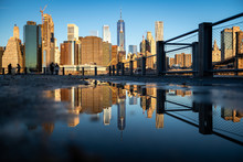 Panorama Of Lower Manhattan Reflected In The Water Puddle On The Walkway Of Brooklyn Bridge Park, Pier 1.