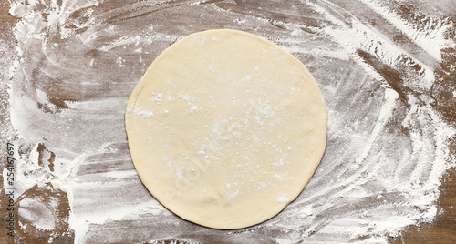 Raw rolled out pizza dough on floured surface