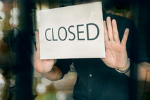 Man Putting Closed Sign In Window In Shop. Late At Night In City.