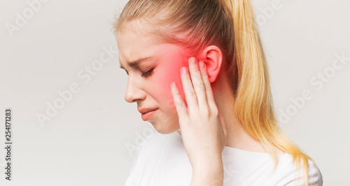 Woman having ear pain, touching her painful head