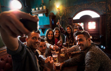 Group Of Millennial People Takes A Selfie In A Pub Drinking Beer
