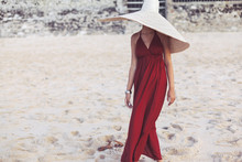 Elegant Lady In Straw Hat And Red Dress On Beach