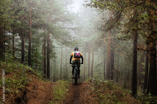 cyclist with backpack riding mountainbike on forest trail in fog Canvas Print