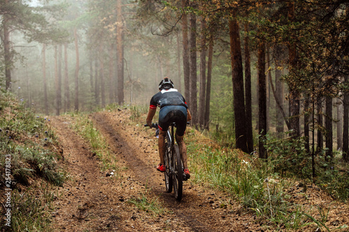Photo  cyclist on mountain bike riding uphill on forest trail in fog