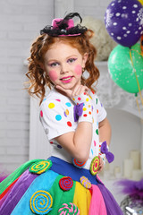 A little girl in bright color carnival clothes, with bright make-up.