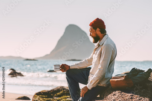 Man relaxing at ocean beach holding tea cup solo traveling lifestyle adventure summer vacations in Norway breakfast outdoor