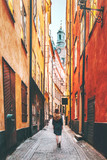 Fototapeta Uliczki - Woman tourist walking alone in Stockholm narrow street traveling lifestyle summer vacations in Sweden