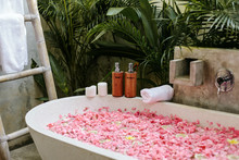 Bath Tub With Flower Petals, Towel And Beauty Products