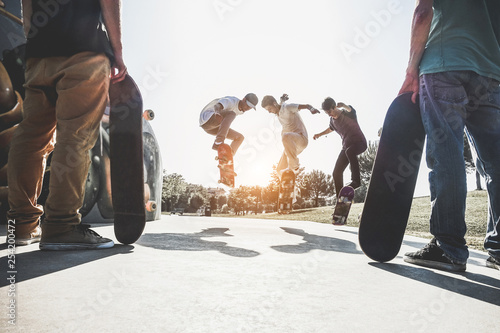 Skaters jumping with skateboard in city skate park - Main focus on center guys heads