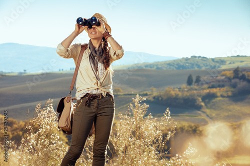 Fotografia  solo tourist woman looking into the distance through binoculars