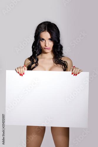 Photo seductive naked brunette woman holding empty board