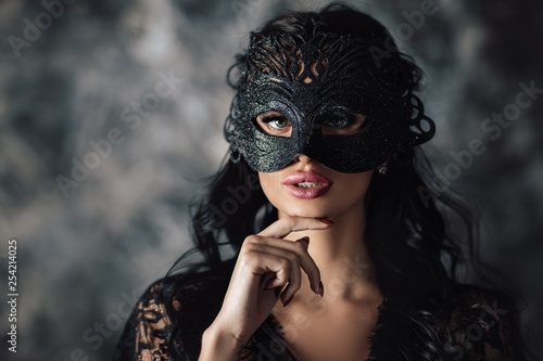 Fototapeta portrait of sexy beautiful woman in lace black erotic lingerie and carnival mask on dark background obraz