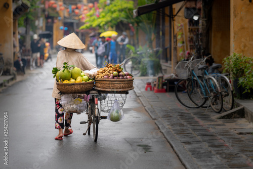 Canvastavla  Woman walking in Hoi An with fruits