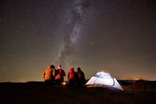 Summer Camping In The Mountains. Back View Of Happy Friends Hikers Having A Rest Together Around Campfire Near Glowing Tourist Tent At Night. On Background Night Starry Sky Full Of Stars And Milky Way
