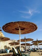 Beach Straw Umbrella Against The Sky. Outdoor