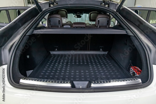Fotografie, Obraz  White luggage space in the body of the SUV hatchback with open rear doors and le