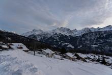 Abendhimmel Mit Wolken über Bergdorf Im Schweizer Skiort Hohfluh Im Hasliberg. Sicht Vom Wegesrand über Schneebedeckte Piste Ins Tal Hinunter.