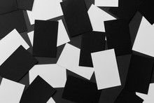 Top View Mockup Of White And Black Horizontal Business Cards Scattered At Black Textured Paper Background.