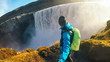 Iceland - Man taking selfie with the waterfall.