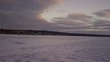Drone flying towards shoreline on a frozen lake during sunset.