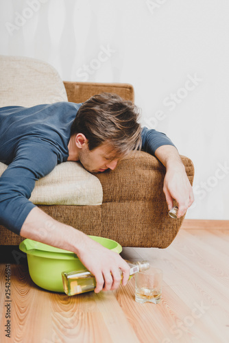 Fotografía  Alcoholic man lying on couch and pouring whiskey from bottle to glass
