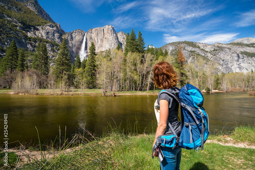 Photo  Young woman wearing a backpacking is admiring Yosemite falls near Merced river i