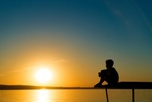 Small Boy Sitting Alone On The Footbridge Holding His Legs And Dreaming At Sunset. Little Kid Watches The Sun Setting Over The River.