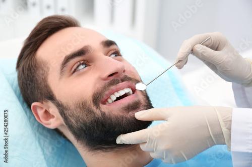 Fotografia  Dentist examining young man's teeth with mirror in hospital