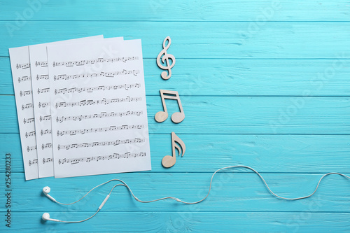 Earphones, music notes and sheets on wooden background, flat lay. Space for text - 254280233