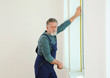 Service man measuring window for installation indoors. Space for text