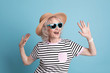 canvas print picture - Portrait of mature woman in hipster outfit on color background