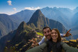 Happy couple backpackers traveling in front of Machu Picchu. taking selfie in front of the ruins of the ancient city. Cusco, Peru travel