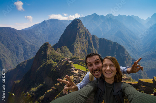 Photo  Happy couple backpackers traveling in front of Machu Picchu