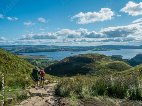 Foto auf Leinwand Blau Jeans two girls hiking with beautiful lake (loch lomond) and green landscape on a sunny day