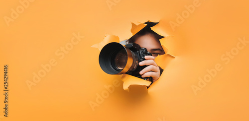 Pinturas sobre lienzo  A teenage girl is holding a black camera with a telephoto lens that looks out through a torn hole in yellow paper