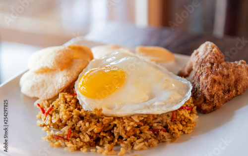 Deurstickers Gebakken Eieren Chilly fried rice with sunny side egg up on white plate. Traditional indonesia and asian food. Selective focus.